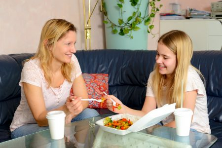 mother and daughter eating together fast food